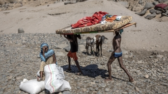 Tigray refugees who fled the conflict in the Ethiopia's Tigray carry their furniture on the banks of the Tekeze River