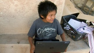 Seven-year-old Jaydon Zeema of the Hopi Tribe in Arizona on the laptop provided by his school.