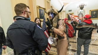 A member of the mob that breached the Capitol waves a finger at police.