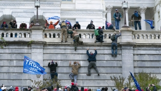 Rioters scale a wall at the U.S. Capitol building