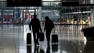 People walk with their luggage through a deserted check-in hall at the airport in Munich, Germany