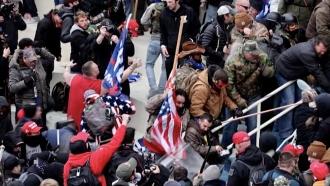 A man uses a flagpole as a weapon.