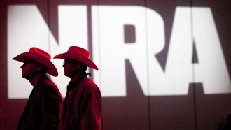 Two cowboy hat wearing NRA members walk in front of the gun groups logo