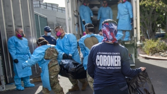 "Coroner Elizabeth ""Liz"" Napoles, right, works alongside with National Guardsmen who are helping to process COVID-19 deaths"