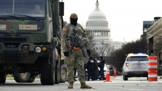 A National Guard member stands at a road block outside the Capitol.
