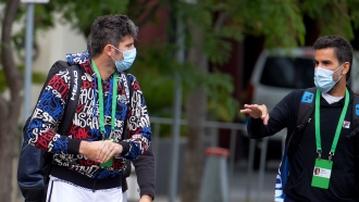 Italian tennis player Simone Bolelli, left, and Argentina's Maximo Gonzalez are escorted to their training session