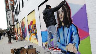 Shawn Perkins spraypaints a mural of Kamala Harris
