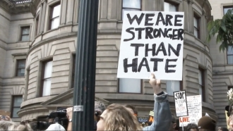 """We are stronger than hate"" sign at a protest"