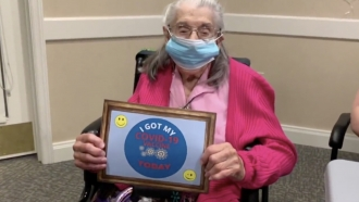Woman holds a sign after getting COVID shot.