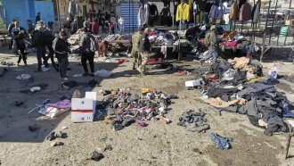 People and security forces gather at the site of a deadly bomb attack in an Iraqi market selling used clothes