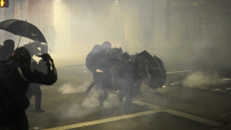 A group of protesters shield themselves from chemical irritants.