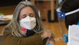 Teacher Lisa Egan is vaccinated with the Moderna coronavirus vaccine at a clinic in New York City