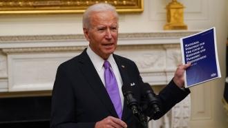 President Joe Biden holds a booklet as he speaks about the coronavirus