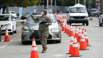 A member of the Florida National Guard directs vehicles at a drive-thru COVID-19 vaccination site at Marlins Park.