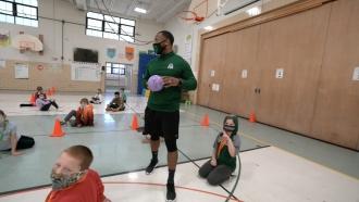 Teacher holds a ball.