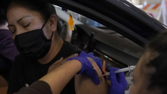 Jamie Yeini receives a shot of the Moderna COVID-19 vaccine at a drive-thru vaccination center in California.