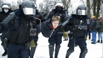 Police detain a man after protests over Alexei Navalny's arrest in Russia