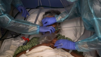 A patient has a ventilator placed on her by two nurses