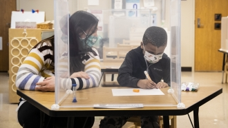 Pre-kindergarten teacher Sarah McCarthy works with a student at Dawes Elementary in Chicago,