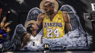 Adam Dergazarian, bottom center, pays his respect for Kobe Bryant and his daughter, Gianna, in front of a mural.