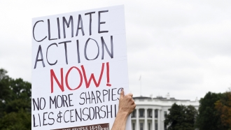 Protesters sign calling for climate action in front of the White House.