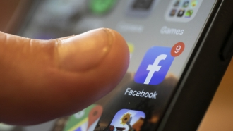 The Facebook app is displayed on the screen of a smartphone