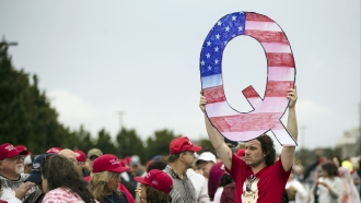 A man holds a giant Q sign at a Trump rally