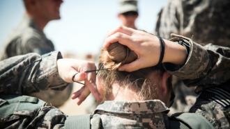 Woman in Army uniform ties back hair