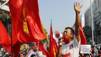 A man uses a loudspeaker to address a crowd of protesters in Mandalay, Myanmar