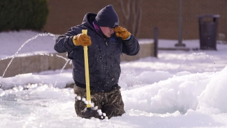 City of Richardson worker Kaleb Love stands in a frozen fountain as he takes a break from clearing ice