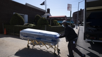 Person pushes casket on gurney