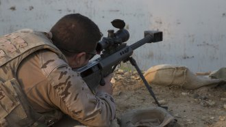 Service member looks in weapon viewfinder