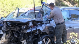 A law enforcement officer looks over a damaged vehicle following a rollover accident involving golfer Tiger Woods