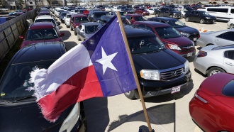 Hundreds of a vehicles are staged in a parking lot as people wait in line at a food and water distribution site