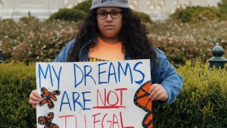 """Undocumented immigrant Andrea Anaya hols a sign saying """"my dreams are not illegal"""""""