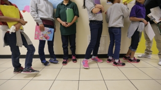 """Migrant teens line up for a class at a """"tender-age"""" facility for babies, children and teens, in Texas' Rio Grande Valley"""