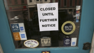 A closure sign due to pandemic is posted at a New Hampshire shop.