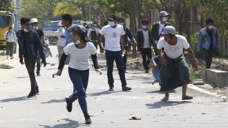 Protesters run from police firing tear gas in Mandalay, Myanmar