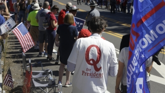 A man in QAnon T-shirt waits for President Donald Trump to arrive in Old Forge, Pennsylvania