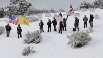 Protesters stand in the snow.