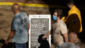 Visitors wearing face masks walk past a sign requiring masks