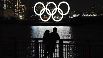A man and a woman stand with the backdrop of the Olympic rings floating in the water.