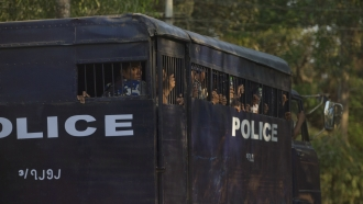 police transport vehicle is driven with detainees, believed to be student protesters.