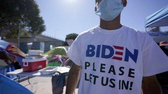 """Man seeking asylum in the U.S. wearing a shirt that reads, """"Biden please let us in."""""""