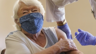 Nathalie Avery, 90, reacts as she gets the COVID-19 vaccine