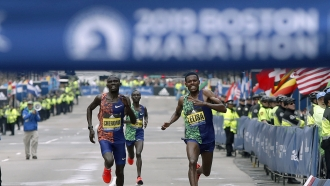 Lawrence Cherono, left, of Kenya, runs to the finish line to win the 123rd Boston Marathon.
