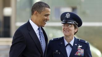 Former President Barack Obama walks with then Col. Jacqueline D. Van Ovost