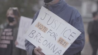 Activist holds Breonna's Law sign