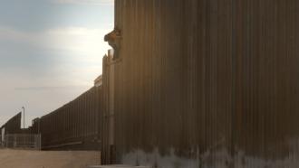 A man scales the border wall in El Paso