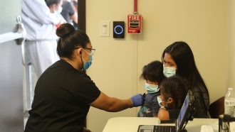 Migrant family is given an initial health screening at a border patrol facility.
